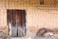 Old traditional style mud brick Korean farm building with wooden doors. Old wooden doors on a traditional Korean mud brick style farm house building Royalty Free Stock Images