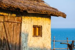Old traditional white croft cottage with thatched roof, with sea in the bay. Concept of isolated beauty, conservation, building wi Stock Photography