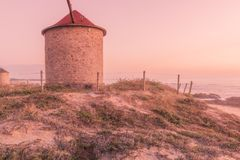 Old traditional wind-mill. In sand-hills of Apulia Portugal stock photo