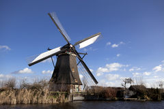 Old, traditional windmill in the Dutch canals. Netherlands.White clouds on a blue sky, the wind is blowing. Stock Photo