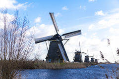 Old, traditional windmill in the Dutch canals. Netherlands.White clouds on a blue sky, the wind is blowing. Royalty Free Stock Photography