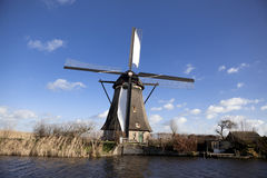 Old, traditional windmill in the Dutch canals. Netherlands.White clouds on a blue sky, the wind is blowing. Stock Images