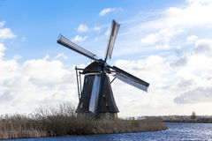 Old, traditional windmill in the Dutch canals. Netherlands.White clouds on a blue sky, the wind is blowing. Stock Photos