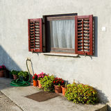 Old traditional window with open wooden shutters and flowers Stock Photos