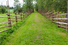 Old traditional wooden fence and road Stock Photos