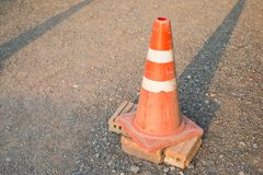 The old traffic cone on the road. The old orange traffic cone on the road forbidden the car pass Stock Photo