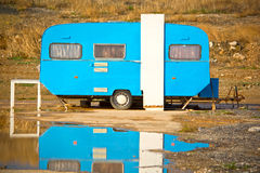 Old trailer caravan. Painted blue, reflected on the puddle royalty free stock photography