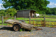 Old trailer. Old rusty trailer at a horse farm. Horses and wooden shed in a background stock photo