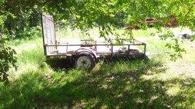 Old Trailer in Yard. An old trailer sitting under a tree in green grass Stock Photography