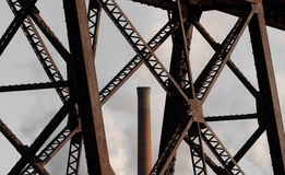 Old Train Bridge and Factory Smokestack Stock Image