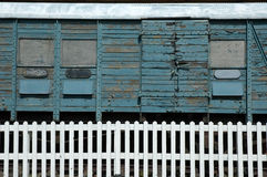 Old train carriage. An old wooden train carriage, faded blue paint flaking off, with white picket fence in front, simple lines and colour Royalty Free Stock Image