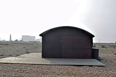 A old train carriage converted into a house with Dungeness Power Station in the background. A landscape view of Dungeness with a carriage converted into a house royalty free stock image