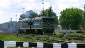 Old train goes through the railway crossing, smokes. The old train goes through the railway crossing, smokes stock footage