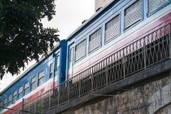 Old train running on railway in Hanoi street.  Stock Photo