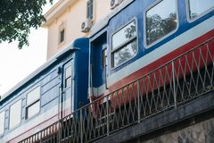 Old train running on railway in Hanoi street.  Royalty Free Stock Images