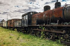 Old train set with a steam locomotive. Old abandoned train set with a steam locomotive standing on some old tracks with grass and bushes growing on it Royalty Free Stock Photo