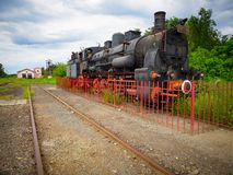 Old train steam locomotive in the older train station in Romania stock images