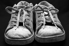 Old trainers on black. An old pair of traing shoes in black and white on black stock photo