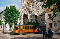 Old tram in Soller in front of medieval gothic cathedral with huge rose window, Mallorca, Spain. Port de Soller, Mallorca, Spain - May 26, 2016: Old tram in Royalty Free Stock Photo