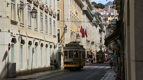 Old trams one by one sneaking through narrow streets of Lisbon carrying people. Stock footage stock footage