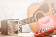 Old transistor radio and Acoustic guitar on wooden background. Royalty Free Stock Photos