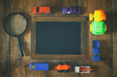 Old transportation toys, blank blackboard and magnifying glass Royalty Free Stock Image