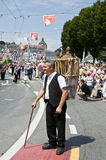 The old transporter. Swiss old man farmer with a stick carrying carboys on his back during the jodler's parade in Luzern, Switzerland. A folkloristic event Royalty Free Stock Photos