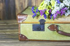 Antique suitcase with flowers. Old travel bag with delicate flowers Stock Photos