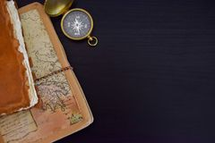Travel Notes with Compass. Old travel notebooks and compass placed on black wood surface Stock Photography