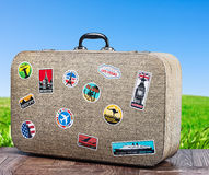 Old travel suitcase on background with grass field Royalty Free Stock Images