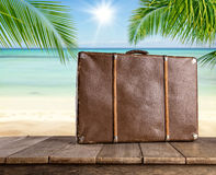 Old travel suitcase on wooden planks. Tropical beach on background Royalty Free Stock Photography