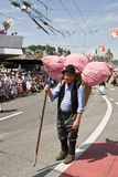 The old traveller. Swiss old man farmer with a stick carrying a huge filled basked on his back during the jodler's parade in Luzern, Switzerland. A folkloristic Royalty Free Stock Photos