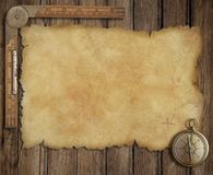 Old treasure map on wooden desk with compass and Stock Photos