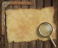Old treasure map on wooden desk with loupe and. Pirates' old treasure map on wooden desk with loupe and ruler Royalty Free Stock Image