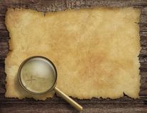 Old treasure map on wooden desk with magnifying Royalty Free Stock Photos