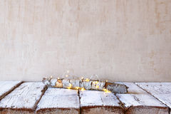 Old tree log with fairy christmas lights on wooden table.selective focus.product display Stock Image