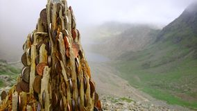 Lucky money tree stump in foreground looking back down mountain on PYG trail on Mount Snowdon in Snowdonia National Park, Wales, U stock image