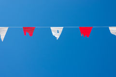 Old triangle flags hung across the  blue sky. Royalty Free Stock Image