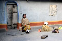 Old tribal Woman Sat in front of her mud house. Environmental Portrait of old tribal lady.