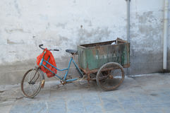 Old tricycle. The wall and flags in Sanhe Ancient town, China during May celebrations. Picture taken May 2014 Royalty Free Stock Photo