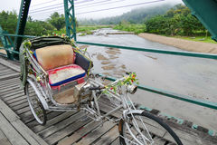 Old tricycle on the wooden footbridge with Royalty Free Stock Image