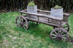 An old trolley or a cart that was harnessed by horses was used to transport and transport various loads, in this case two wooden b. Arrels with grass. Transmits Stock Images