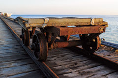 Old trolley on the tracks near the shore of the sea. The boat is in the background Stock Images
