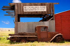 Old Truck and Blacksmith Shop. Horizontal image of an old rusted truck in front of a decaying blacksmith shop.  Old west image against a bright blue sky Stock Photography