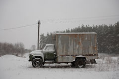 Old truck covered with snow in the woods Stock Photos