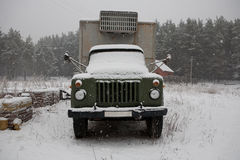 Old truck covered with snow in the woods Royalty Free Stock Photo