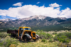 Old Truck Mountain Range. Old abandoned yellow truck sitting in a field in front of the Zapata Mountain Range in southern Colorado with the California Peak in royalty free stock image