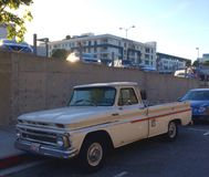 Old truck parked curbside downtown. A old classic cream and red truck parked in a urban setting downtown Stock Photo