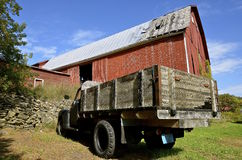 Old truck parked in front of a large barn Stock Images
