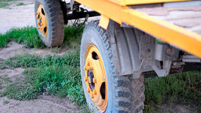 The old truck tire painted in bright yellow color in rural area closeup, selective focus Stock Photos